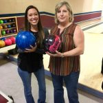 two woman holding bowling balls